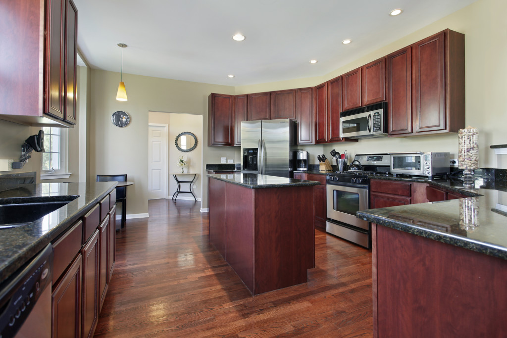 Kitchen in upscale home with cherry wood cabinetry and a narrow cherry wood island