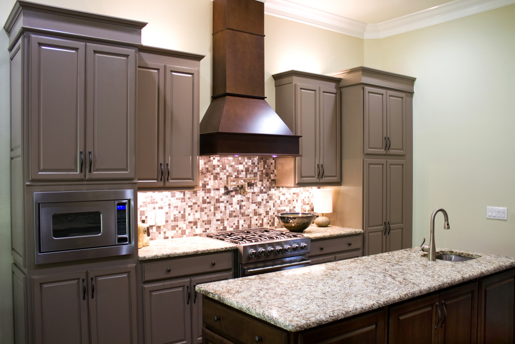 New modern luxury kitchen with narrow island, granite countertops and built in sink & faucet