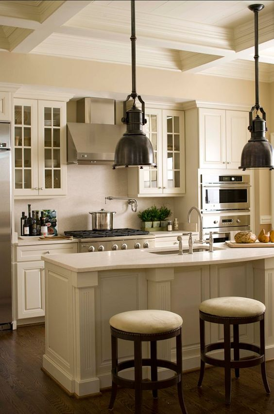 A striking white kitchen with a narrow kitchen island suitable for seating and built in sink